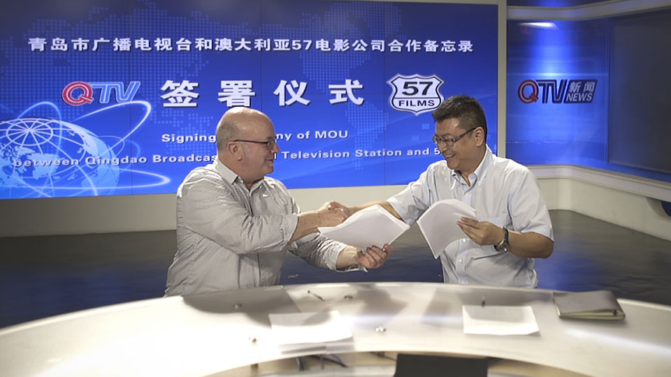 Paul Ryan signing the MOU with Qingdao TV (QTV)
